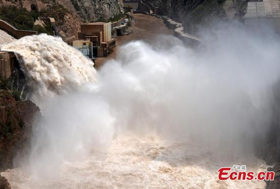 Flood water gushes from the Liujiaxia Reservoir on the Yellow River in Northwest China's Gansu Province. Approximately 2,300 cubic meters of water per second was discharged from the hydroelectric station, as the province has seen record accumulated precipitation in six decades. (Photo: China News Service/ Hou Qi)