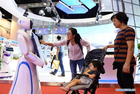 Visitors interact with a robot at the 15th China-ASEAN Expo in Nanning City, south China's Guangxi Zhuang Autonomous Region, Sept. 13, 2018. High-tech exhibits attracted many visitors at the expo. (Xinhua/Lu Bo'an)