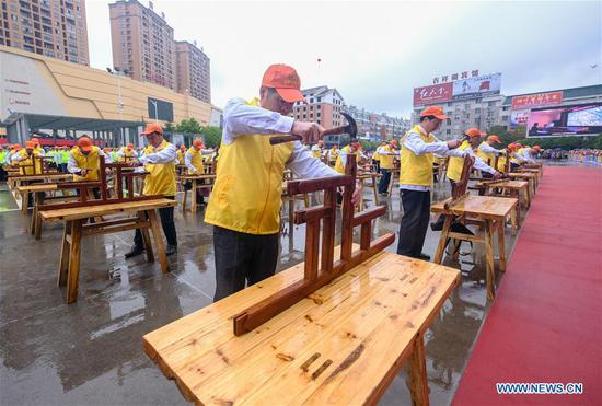 Craftsmen demonstrate skills of making wooden crafts at Huayuan Village of Nanma Town in Dongyang, east China's Zhejiang Province, April 11, 2019. Huayuan is a renowned wooden crafts and mahogany furniture wholesale market in China, as well as a scenic area in the region. (Xinhua/Xu Yu)
