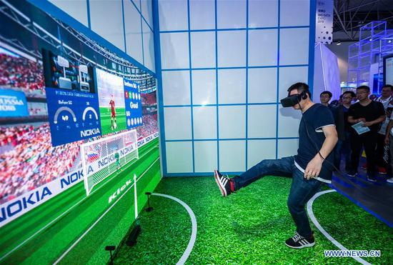 A visitor plays a football game during China International Big Data Industry Expo 2019 in Guiyang, southwest China's Guizhou Province, May 26, 2019. The expo on big data opened Sunday in Guizhou Province, focusing on the latest innovation of the technology and its applications. The four-day expo will be attended by 448 enterprises from 59 countries and regions, according to the organizing committee. (Xinhua/Tao Liang)