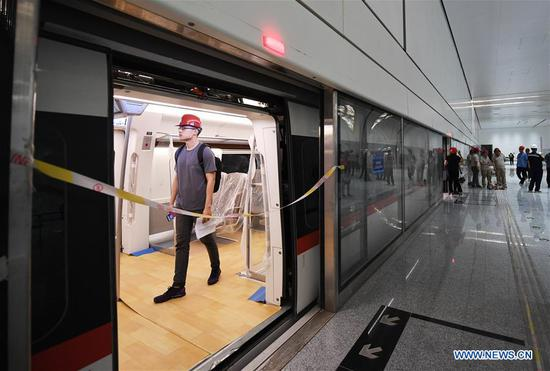 A journalist visits a train of the new airport subway line in Beijing, capital of China, June 15, 2019. Self-driving trains for the subway line connecting downtown Beijing with its new international airport started trial run Saturday, according to local authorities. Stretching 41.4 kilometers, the new line supports autopilot system and can run at a speed of 160 km per hour, with as many as 448 passengers, according to Beijing Major Projects Construction Headquarters Office. (Xinhua/Zhang Chenlin)