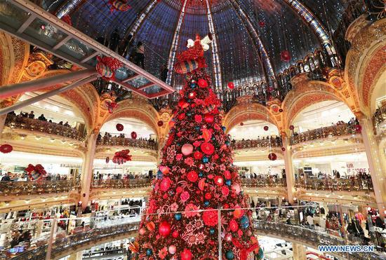 People enjoy the lighted huge Christmas tree at Galeries Lafayette department store in Paris, France, Nov. 24, 2019. The city of Paris is decorated with Christmas trees and decorations for the festival season. (Xinhua/Gao Jing)