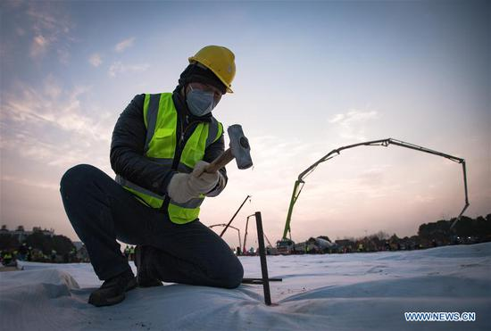 A laborer works at the construction site of Huoshenshan Hospital in Wuhan, central China's Hubei Province, Jan. 28, 2020. The construction of Huoshenshan Hospital, a makeshift hospital for treating patients infected with the novel coronavirus, is underway in Wuhan. (Xinhua/Xiao Yijiu)