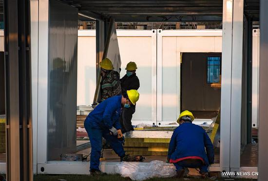 Workers from China Construction Third Engineering Bureau Co., Ltd. are seen at the construction site of Leishenshan (Thunder God Mountain) Hospital in Wuhan, central China's Hubei Province, Jan. 30, 2020. Wuhan is building two hospitals to treat pneumonia patients infected with the novel coronavirus. As of Thursday noon, about 40 percent of the Leishenshan Hospital has been completed, and it is expected to be put into use on Feb. 5. (Xinhua/Xiao Yijiu)
