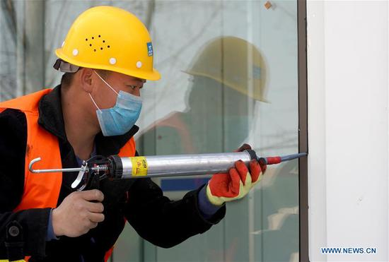 A man works at the construction site of an infectious disease hospital of Zhengzhou First People's Hospital in Zhengzhou, central China's Henan Province, Feb. 4, 2020. The infectious disease hospital is close to be delivered after days of construction work for admitting patients infected with the novel coronavirus (2019-nCoV). (Xinhua/Li An)