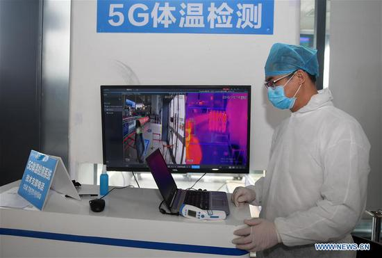 A staff member operates a 5G body temperature screening system at Nanning East Railway Station in Nanning City, south China's Guangxi Zhuang Autonomous Region, Feb. 13, 2020. The 5G body temperature screening system, which is able to automatically check passengers' body temperature and issue warnings, has been put into use in Nanning East Railway Station to help fight the novel coronavirus epidemic. (Xinhua/Lu Boan)