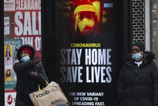 "Passengers wearing face masks stand next to an advertising board reading ""Stay Home Save Lives"" at a bus stop in London, Britain, Jan. 10, 2021. (Xinhua/Han Yan)"