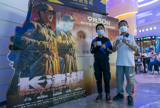 """Two boys pose for a photo in front of a poster board for """"The Battle at Lake Changjin"""" at a theater in Kunming, southwest China's Yunnan Province, Oct. 1, 2021. (Xinhua/Chen Xinbo)"""