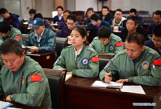 Jiang Dandan (C) takes part in a flight mission coordinating meeting in Yanliang District of Xi'an, capital of northwest China's Shaanxi Province, on March 6, 2019. Jiang Dandan, 29, is one of the youngest test pilots in China and the only female test pilot for commercial transport aircrafts currently being trained at the Aviation Industry Corporation of China, Ltd. She went through dozens of professional courses and 750 hours of flying practice in six years. At the end of 2017, she became a test pilot and participated in the test flights during the research and development of ARJ21-700, C919 and other types of aircrafts. (Xinhua/Shao Rui)
