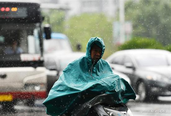 A man rides in rain in Xiqing District of Tianjin, north China, on May 26, 2019. A rainfall hit the city Sunday. (Xinhua/Li Ran)