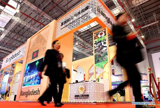 Visitors walk past the Bangladesh pavilion during the second China International Import Expo (CIIE) in Shanghai, east China, Nov. 5, 2019. The second CIIE kicked off Tuesday at the National Exhibition and Convention Center in Shanghai. (Xinhua/Chen Fei)