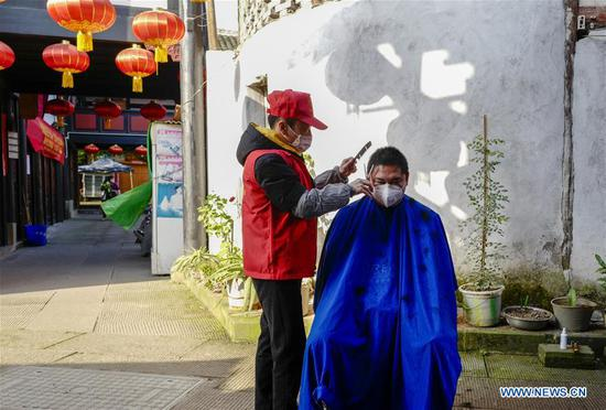 A volunteer barber cuts a man's hair at a community in southwest China's Chongqing Municipality, Feb. 16, 2020. Since the outbreak of the novel coronavirus, most barbershops have been closed. A community in Beibei District of Chongqing organized a team of volunteer barbers to provide free haircuts for its residents. (Xinhua/Liu Chan)
