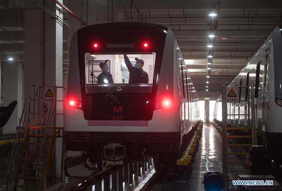 Staff overhaul a subway train at a train depot in Wuhan, central China's Hubei Province, March 23, 2020. Wuhan is making preparations for restoring the operation of public transportation. The public need to go through real-name registration for taking public transportation or taxis in Wuhan, capital of central China's Hubei Province, authorities said Sunday. (Xinhua/Xiao Yijiu)