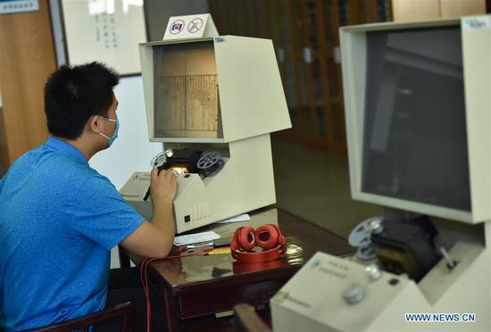 A reader reads an ancient book on a microfilm reader at the National Library of China in Beijing, capital of China, May 12, 2020. The southern area of the National Library of China reopened to the public on Tuesday. Visitors need to make reservations via the social media application Wechat or phone calls, according to a notice from the library. (Xinhua/Chen Zhonghao)