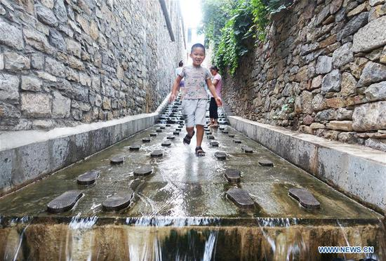 A young tourist visits a scenic resort in Zaozhuang, east China's Shandong Province, June 27, 2020. China saw around 48.81 million domestic tourist trips made during the Dragon Boat Festival holiday, bringing in 12.28 billion yuan (around 1.74 billion U.S. dollars), the Ministry of Culture and Tourism said Saturday. (Photo by Li Zongxian/Xinhua)
