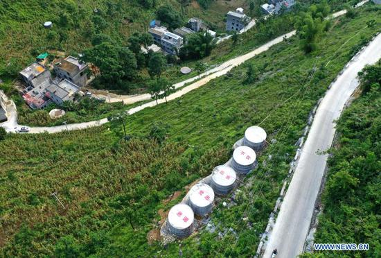 Aerial photo taken on July 22, 2020 shows the newly-built water tanks in Anlan Village of Du'an Yao Autonomous County, south China's Guangxi Zhuang Autonomous Region. South China's Guangxi Zhuang Autonomous Region, home to the country's largest ethnic minority population, has lifted all its 54 poverty-stricken counties out of poverty. The last eight impoverished counties in the region, including six ethnic minority autonomous counties, have eliminated absolute poverty, the regional government announced on Friday. (Xinhua/Zhou Hua)