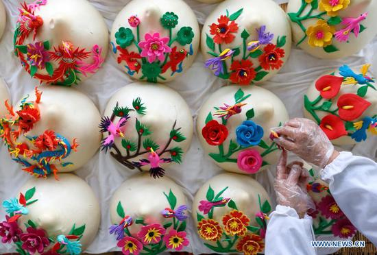 A villager makes Huamo, steamed buns with elaborate flowery decorations, in Xiwang Village of Tianheng Township, Jimo District, Qingdao, east China's Shandong Province, Feb. 1, 2021. Lunar New Year ranks among the most important festivals in China, and the celebrations are multifaceted, including food. When the Lunar New Year comes, people across China make a variety of snacks which they believe will bring good fortune. (Photo by Liang Xiaopeng/Xinhua)