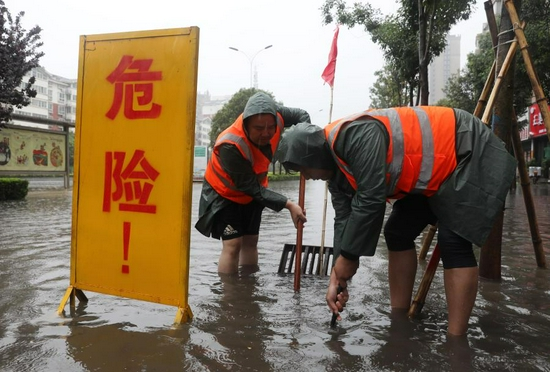 Staff members drain water at a waterlogged area in Wuzhi County, central China's Henan Province, July 20, 2021. (Photo by Feng Xiaomin/Xinhua)