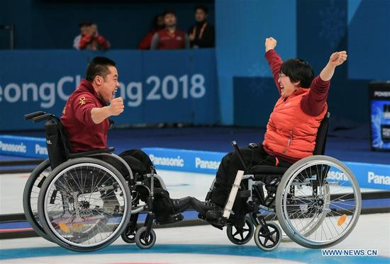 China's Liu Wei (L) and Wang Meng celebrate after winning the wheelchair curling final against Norway at the 2018 PyeongChang Winter Paralympic Games at Gangneung, South Korea, March 17, 2018. China beat Norway in the final 6-5 to claim the title of the event, which is also China's first-ever Winter Paralympic medal with gold. (Xinhua/Wang Jingqiang)