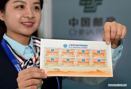 A postal worker displays a sheet of postage stamps commemorating the 18th Shanghai Cooperation Organization (SCO) summit at the media center of the summit in Qingdao, east China's Shandong Province, June 9, 2018. China Post issued a commemorative stamp here on Saturday to mark the 18th SCO summit. (Xinhua/Li Ziheng)
