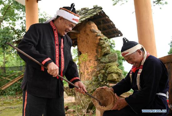 Villagers Pan Zhenwu (L) and Pan Zhiming make a Huangni drum in Jinxiu Yao Autonomous County, south China's Guangxi Zhuang Autonomous Region, Aug. 1, 2018. The local Huangni drum dance was listed as one of the national intangible cultural heritage in 2011. (Xinhua/Lu Boan)