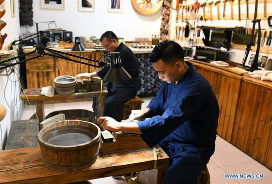 Yan Min (back) restores ancient weapons with his son in Shijiazhuang, north China's Hebei Province, Sept. 11, 2018. Yan Min, dedicated to ancient weapon restoration for more than 30 years, has hitherto repaired over 500 pieces of ancient weapons with his son Yan Peng. Influenced by his father, Yan Peng quit his job and embarked on restoring ancient weapons in the year of 2015. The sophisticated craftsmanship of ancient weapon restoration embodies working procedures of polishing, burnishing, grinding etc.