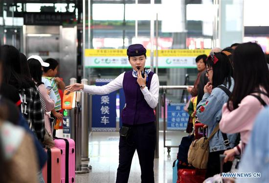 A staff member instructs passengers to line up at Hefei South Railway Station in Hefei, east China's Anhui Province, Oct. 7, 2018. A travel peak is seen around China on Sunday, the last day of the week-long National Day holidays. (Xinhua/Liu Junxi)