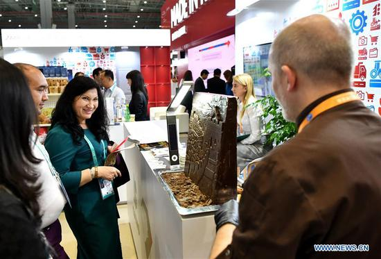 Visitors learn about Russian chocolate during the first China International Import Expo (CIIE) in Shanghai, east China, Nov. 6, 2018. Various foods from all over the world are exhibited in the CIIE. (Xinhua/Li Xin)