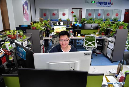 At 9:04 pm, Li Xin, a cameraman of the official website of Xiongan New Area, edits videos in the newsroom in Xiongan New Area, north China's Hebei Province, April 1, 2019. Known as the China's