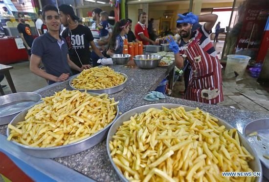 A vendor sells food in an amusement park during celebrations of Eid al-Fitr in Beirut, Lebanon, on June 4, 2019. (Xinhua/Bilal Jawich)