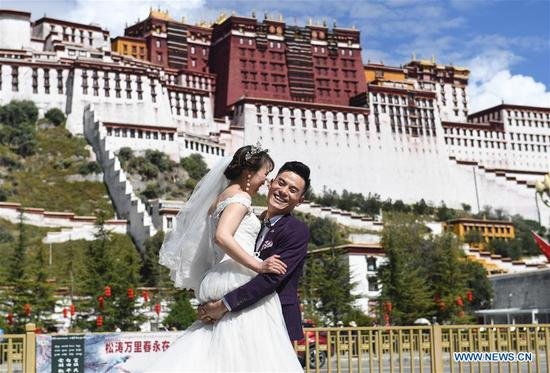 A couple poses for wedding photos on the square of the Potala Palace during the National Day holiday in Lhasa, capital of southwest China's Tibet Autonomous Region, Oct. 6, 2019. (Xinhua/Jigme Dorje)