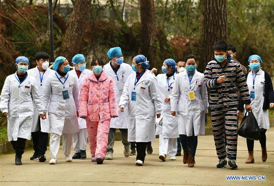 Cured patients accompanied by medical staff walk out of the Jiangjunshan section of the public health center for treatment in Guiyang, southwest China's Guizhou Province, Feb. 5, 2020. Three pneumonia patients infected with the novel coronavirus were cured and discharged from the hospital on Wednesday. (Xinhua/Yang Wenbin)