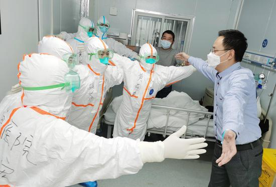 """Mr. Wang, 36, a recovered COVID-19 patient, """"hugs"""" medical staff without body contact before leaving Leishenshan (Thunder God Mountain) Hospital in Wuhan, capital of central China's Hubei Province, Feb. 18, 2020. (Photo by Gao Xiang/Xinhua)"""