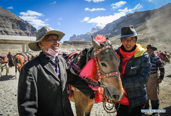 People of Gangsha Village wait for pilgrims at the starting of a travel to Mount Kangrinboqe in Ali Prefecture, southwest China's Tibet Autonomous Region, June 24, 2018. Gangsha Village is located at the foot of Mount Kangrinboqe, a sacred Hindu and Buddhist site in Ali. Since the 1980s, local farmers and herdsmen have started to receive pilgrims and tourists from home and abroad. They upgraded services of tourism industry in the past 30 years, and tourism increased villagers' income. (Xinhua/Liu Dongjun)