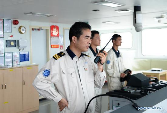 Captain Chen Xiangwu (1st L) gives orders while participating in an emergency drill on the Tian'en vessel of China's COSCO Shipping Specialized Carriers Co., Ltd. during its journey to Europe through the
