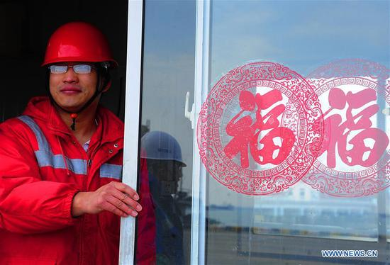 Gong Fuqiang, a crane driver, looks out of the door of a rest room at Zhenghe Xinggang Terminals of Taicang Port in Suzhou, east China's Jiangsu Province, Feb. 11, 2019, the first workday after Spring Festival holiday. (Xinhua/Ji Haixin)
