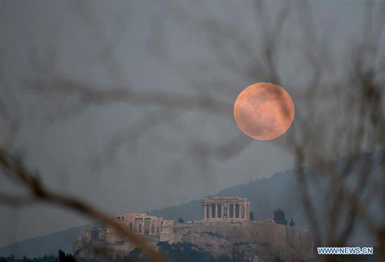 A full moon is seen over the Acropolis in Athens, Greece, on Feb. 19, 2019. (Xinhua/Marios Lolos)