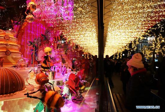 A girl enjoys the Christmas window at Galeries Lafayette department store in Paris, France, Nov. 14, 2019. The city of Paris is decorated with Christmas trees and decorations for the festival season. (Xinhua/Gao Jing)