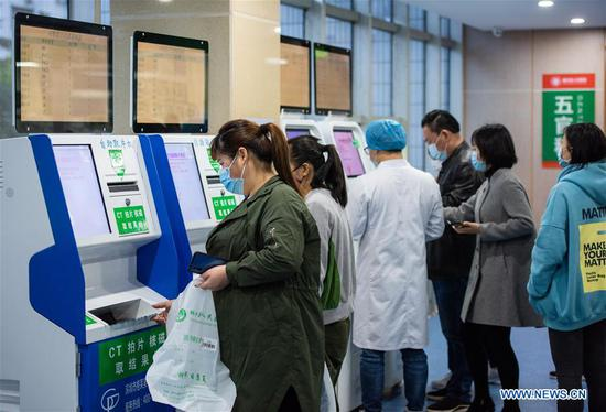 People print medical reports with self-service machines at a hospital in Zigui County of Yichang, central China's Hubei Province, March 27, 2020. The normal medical services in Zigui have been gradually resumed as the coronavirus epidemic wanes. (Photo by Wang Jiaman/Xinhua)