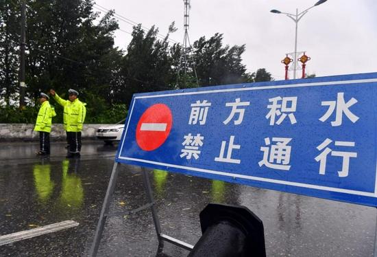Policemen direct traffic at a waterlogged area in Jiaozuo, central China's Henan Province, July 20, 2021. (Xinhua/Li Jianan)