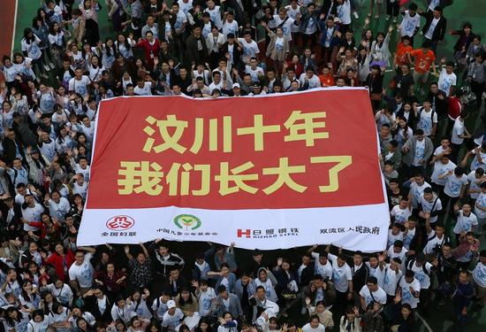"Children orphaned by the devastating earthquake and volunteers return to the Ankang Home to mark the 10th anniversary. The huge banner reads: ""Ten years since Wenchuan earthquake, we have grown up."""