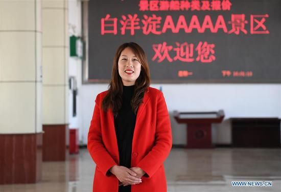 At 4 pm, Zhu Fang, a staff member of Baiyangdian scenic area, stands in the ticket hall in Xiongan New Area, north China's Hebei Province, April 1, 2019. Known as the China's