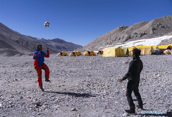 The mountain guide Zhaxi Dondrup plays football at the base camp of the northern face of Mount Qomolangma in southwest China's Tibet Autonomous Region, April 26, 2019. Every year, for a few weeks, hundreds of climbers and supporting personnel come to the base camp of the northern face of Mount Qomolangma, trying to reach the summit of the tallest and most famous mountain in the world. Before starting climbing, they need to hike several times between elevations from 5,000 meters to 7,000 meters, giving their bodies some time to adapt. When this process is over, it's all up to the weather. The base camp is a popular place to wait for the window. Among the six camps on the northern face, the base camp at an altitude of 5,200 meters is the furthest cars can reach and therefor the most equipped. Besides food and accommodation, climbers can also enjoy tea and massage. They can also play football on perhaps the highest field. There's even a simple gym in the camp. Environmental protection is a priority here. Garbage sacks are given to each climbing team. Special containers are put in every camp to collect trash and sewage. The collected trash must be treated 100 kilometers away, and the only road is a zigzagging track. It is not trucks, but yaks that are generally used to make the journey. Actually yaks are vital on the mountain. Beyond the base camp, yak is the only reliable transport. (Xinhua/Sun Fei)