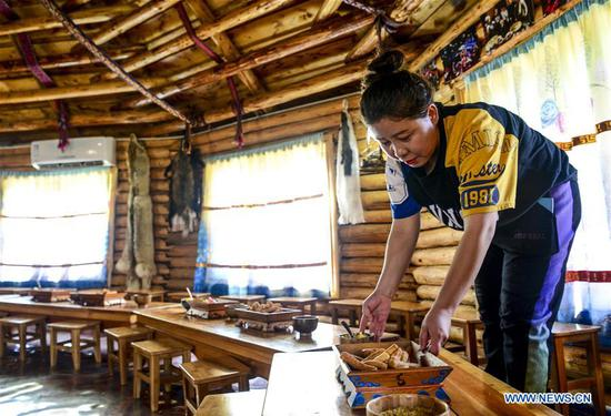 A woman of a homestay prepares for customers at kanas scenic spot in Altay, northwest China's Xinjiang Uygur Autonomous Region, Sept. 25, 2019. More and more tourists choose to experience homestay with strong local characteristic in Xinjiang. (Xinhua/Wang Fei)