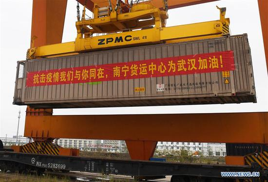 A container carrying supplies for Hubei Province is lifted at a railway port in Nanning, south China's Guangxi Zhuang Autonomous Region, Feb. 4, 2020. The second batch of cargo train loaded with vegetables and fruits set out from Nanning to aid Hubei in its fight against novel coronavirus pneumonia. (Xinhua/Lu Boan)