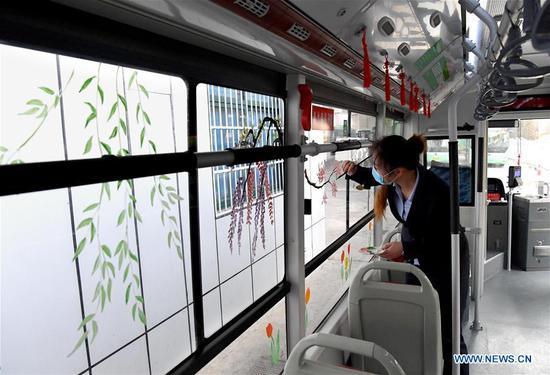 Liu Xiangjie draws flowers on the bus window in Zhengzhou, central China's Henan Province, March 23, 2020. Liu Xiangjie works as the bus conductor of the bus line S105 run by Zhengzhou Bus Communication Corporation. She has painted patterns of flowers on the bus window recently as spring comes. (Xinhua/Li An)