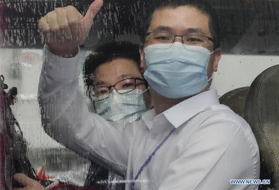 A member of a mainland nucleic acid test support team thumbs up to Hong Kong residents on a bus in Hong Kong, south China, Sept. 16, 2020. (Xinhua/Wang Shen)