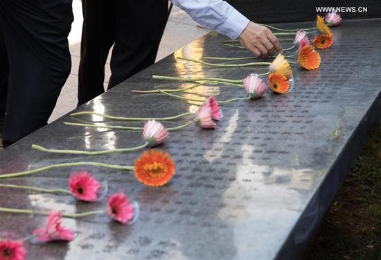 A person lays a flower in front of the monument marking the victory in the Chinese People's War of Resistance against Japanese Aggression and Taiwan's recovery from Japanese occupation during a commemorative event in Taipei, southeast China's Taiwan, Oct. 25, 2020. (Xinhua/Jin Liwang)
