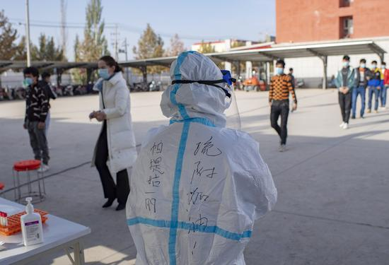 A medical worker stands by as people line up to have their samples collected for nucleic acid testing in Shufu County of Kashgar Prefecture, northwest China's Xinjiang Uygur Autonomous Region, Oct. 26, 2020. (Xinhua/Hu Huhu)