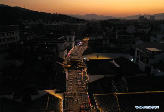 Aerial photo taken on Nov. 10, 2020 shows a night market in Shouchang Township of Jiande City, east China's Zhejiang Province. Shouchang, a small town in mountainous area of Zhejiang, has set up a special night market bringing together night-time booths and more than 30 restaurants, in an effort to enrich people's leisure time and boost local economy. The night market has received over 720,000 tourist trips and raked in 76.33 million yuan (about 11.57 million U.S. dollars) since it opened during the Labor Day holiday. (Xinhua/Weng Xinyang)